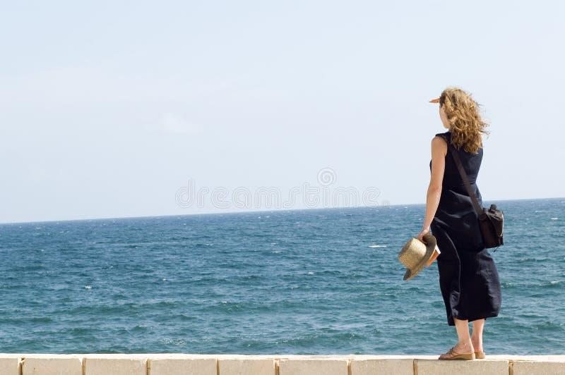 Mujer que permanece en la pared, mirando en el mar fotografía de archivo