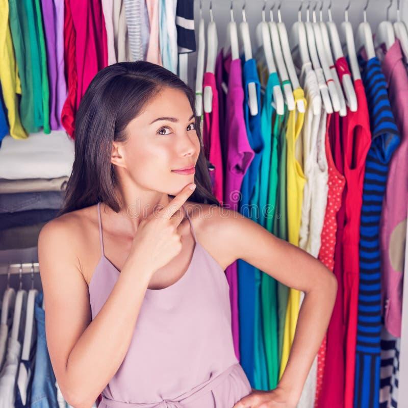Mujer que piensa eligiendo el equipo en armario que hace compras fotos de archivo