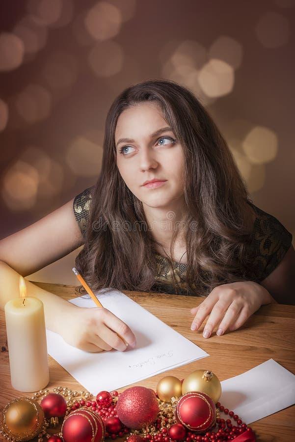 Mujer que piensa y que escribe para la Navidad fotografía de archivo