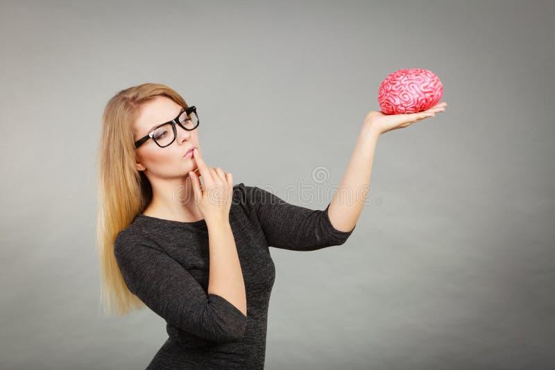 Mujer que piensa y que sostiene el cerebro falso fotografía de archivo libre de regalías