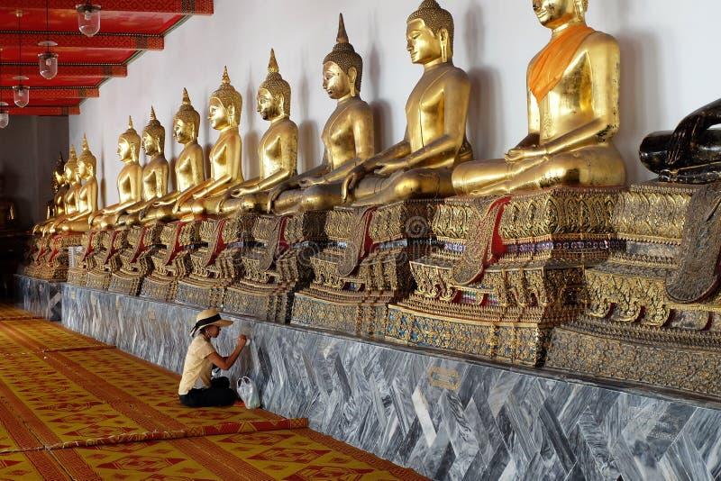 Mujer que pinta las estatuas de Buda en Wat Pho Temple Bangkok, Tailandia imagen de archivo