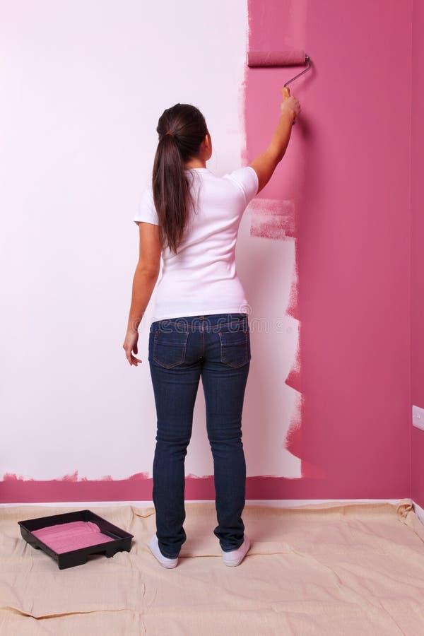 Mujer que pinta una opinión trasera de la pared imágenes de archivo libres de regalías
