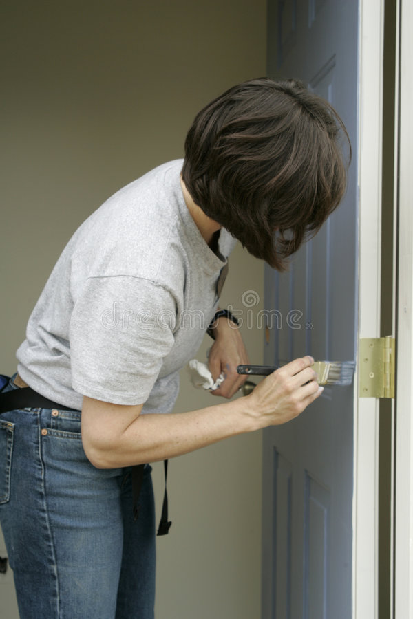 Mujer que pinta una puerta imágenes de archivo libres de regalías