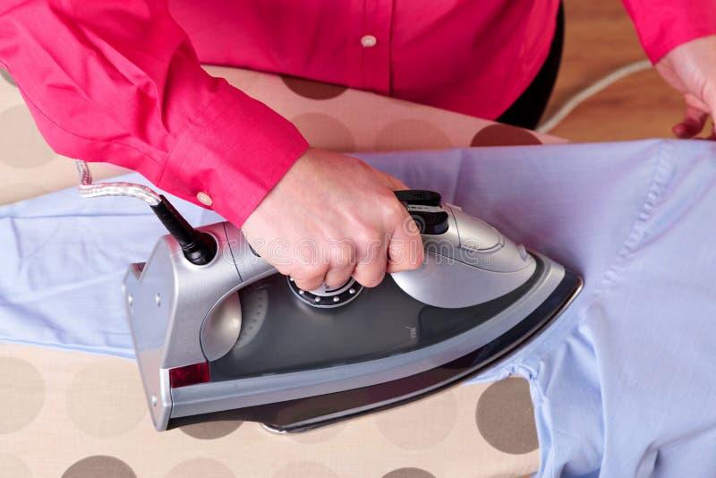 Mujer que plancha una camisa imágenes de archivo libres de regalías