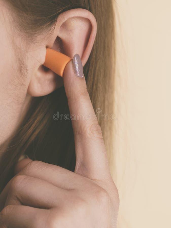Mujer que pone auriculares en los oídos foto de archivo