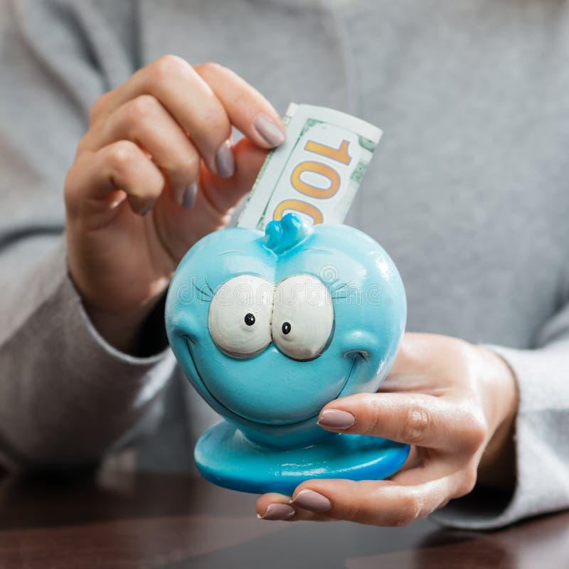 Mujer que pone cientos billetes de banco del euro en un moneybox azul divertido fotos de archivo libres de regalías