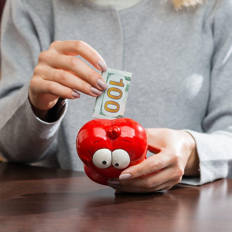 Mujer que pone cientos billetes de banco del euro en un moneybox rojo divertido foto de archivo libre de regalías