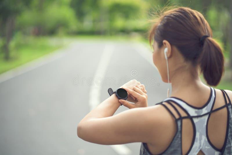 Mujer que pone el reloj elegante de la aptitud para correr Deportista que comprueba el dispositivo del reloj Corredor joven de la foto de archivo libre de regalías