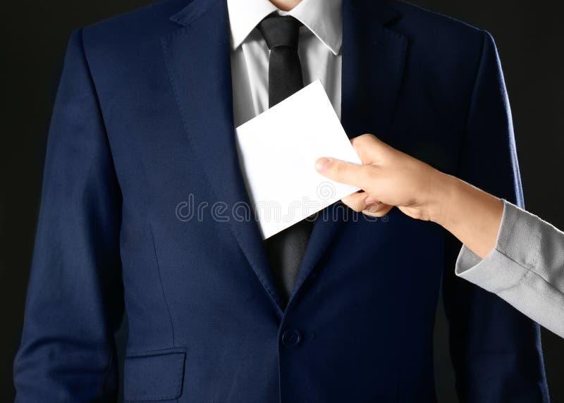 Mujer que pone el soborno en bolsillo del ` s del hombre de negocios, fotografía de archivo