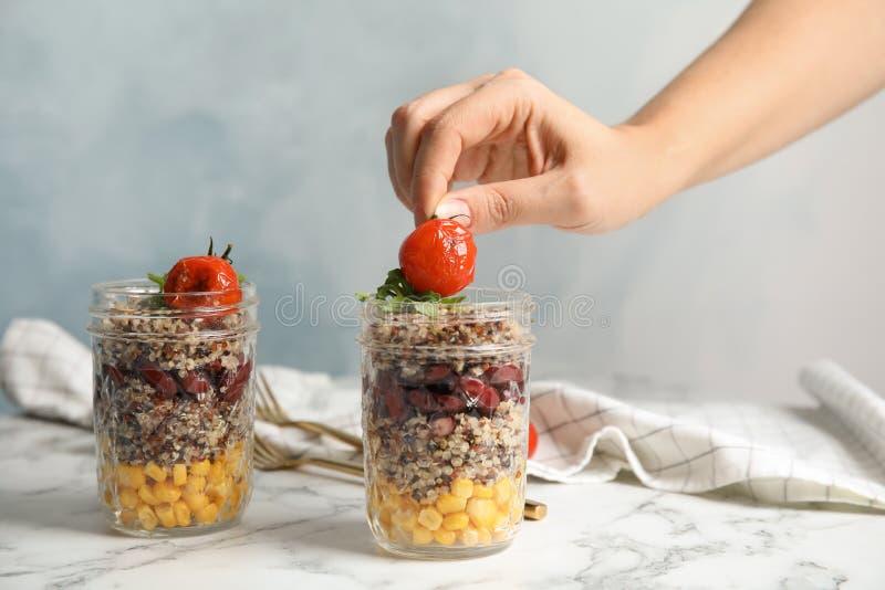 Mujer que pone el tomate en el tarro con la ensalada y las verduras sanas de la quinoa en la tabla imagen de archivo