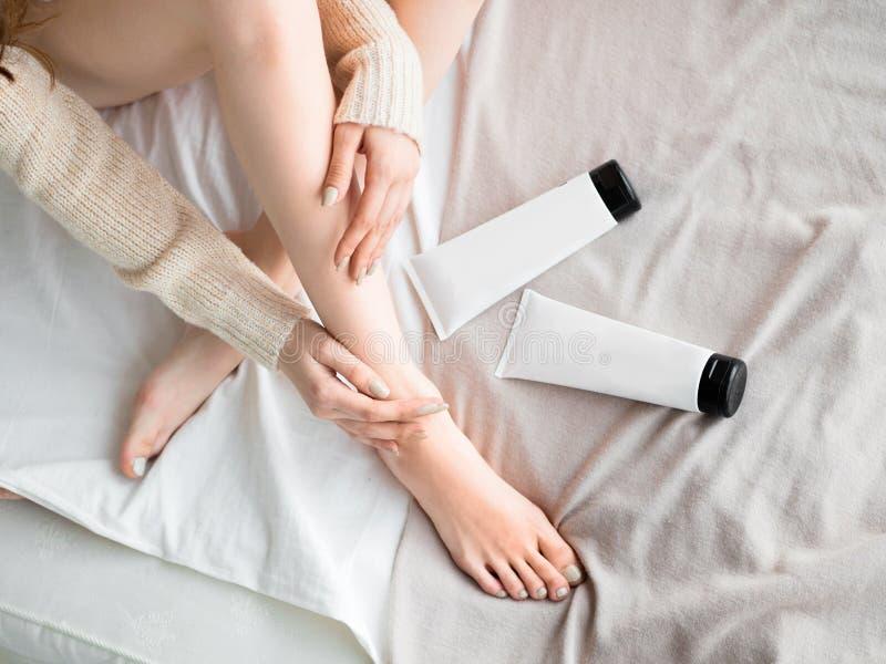 Mujer que pone el ungüento o la crema de la crema hidratante en sus piernas Mofa para arriba Concepto del cuidado de piel fotos de archivo libres de regalías