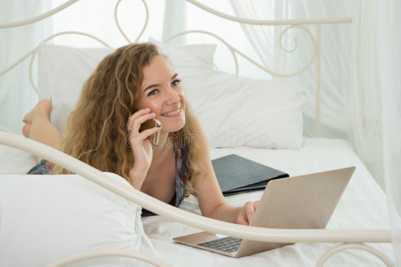 Mujer que pone en cama y que usa el ordenador portátil y el teléfono fotos de archivo