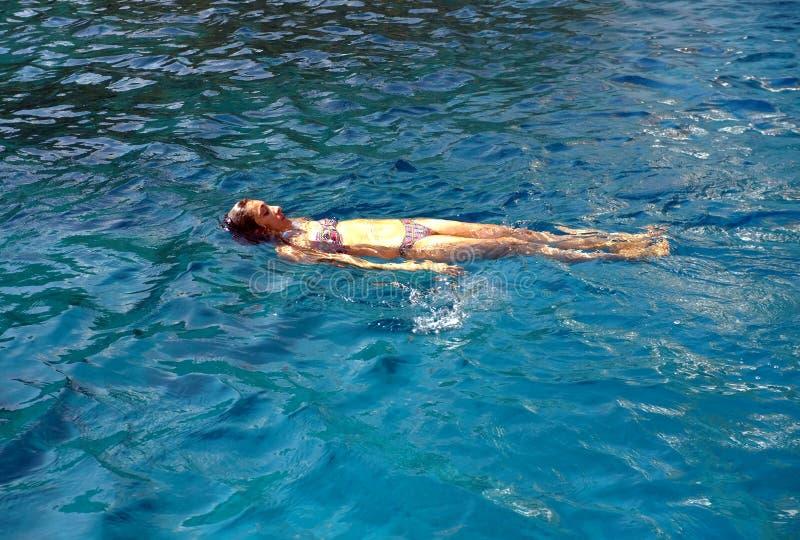 Mujer que pone en el agua foto de archivo