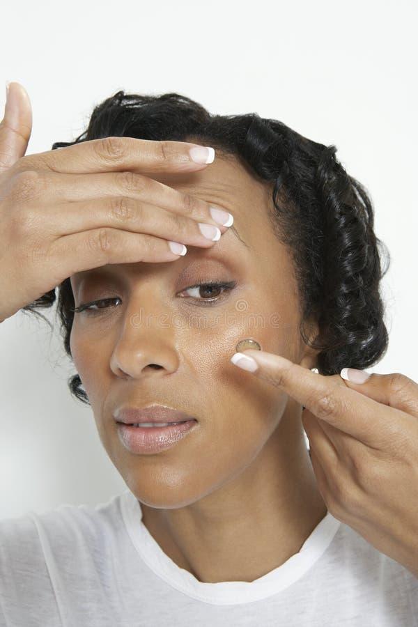 Mujer que pone en la lente de contacto fotos de archivo libres de regalías