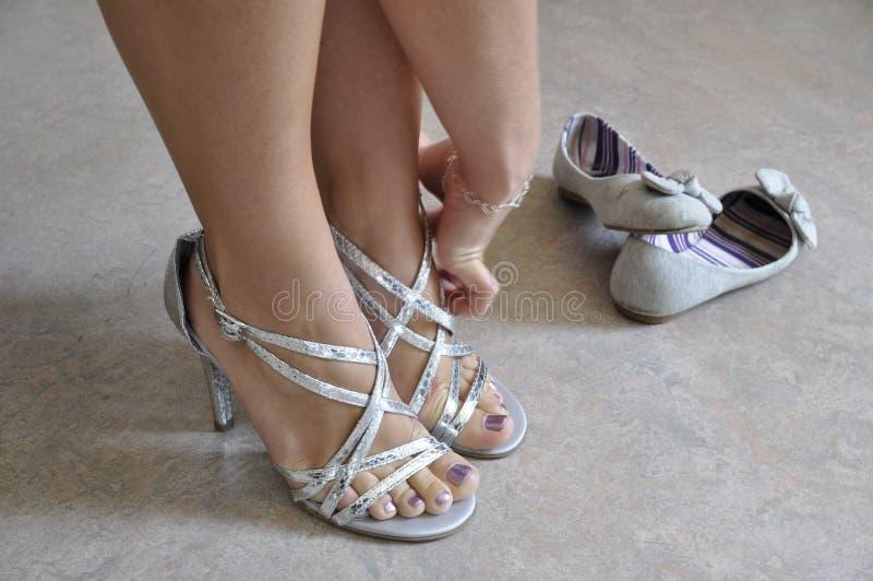 Mujer que pone en los zapatos elegantes fotografía de archivo libre de regalías
