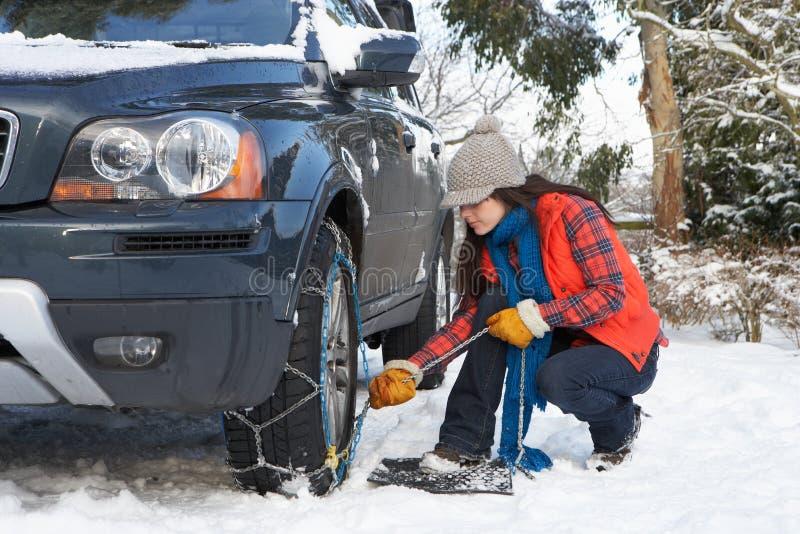 Mujer que pone encadenamientos de nieve sobre el neumático del coche fotografía de archivo libre de regalías
