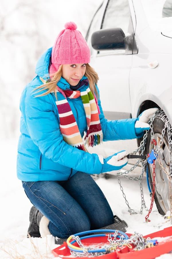Mujer que pone encadenamientos en los neumáticos del invierno del coche imágenes de archivo libres de regalías