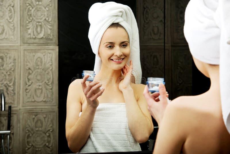 Mujer que pone la crema antienvejecedora en su cara imagenes de archivo