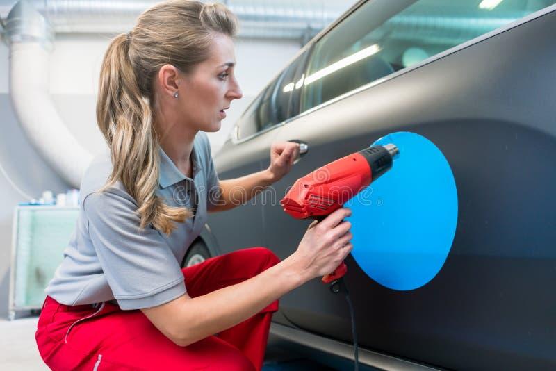 Mujer que pone la etiqueta engomada con lema de la compañía en un coche foto de archivo libre de regalías