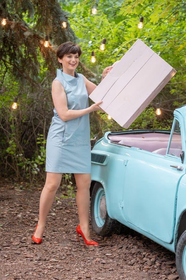 Mujer que pone la maleta en vintage o coche retro imagenes de archivo