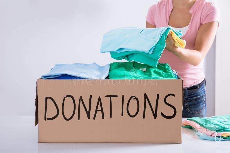 Mujer que pone la ropa dentro de la caja de la donación imagen de archivo