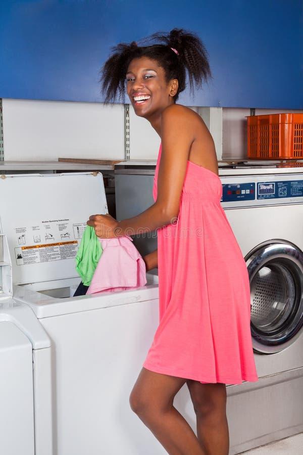 Mujer que pone la ropa en lavadora imagen de archivo libre de regalías