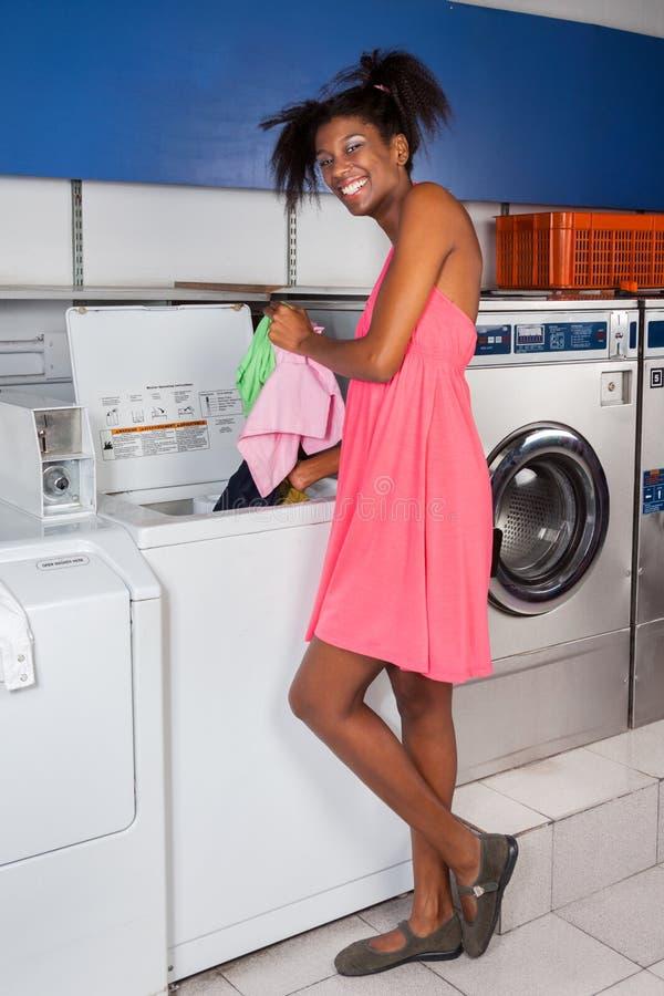Mujer que pone la ropa en lavadora imágenes de archivo libres de regalías
