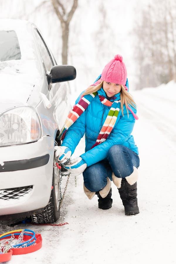Mujer que pone la rueda de coche de los encadenamientos de neumático del invierno fotografía de archivo