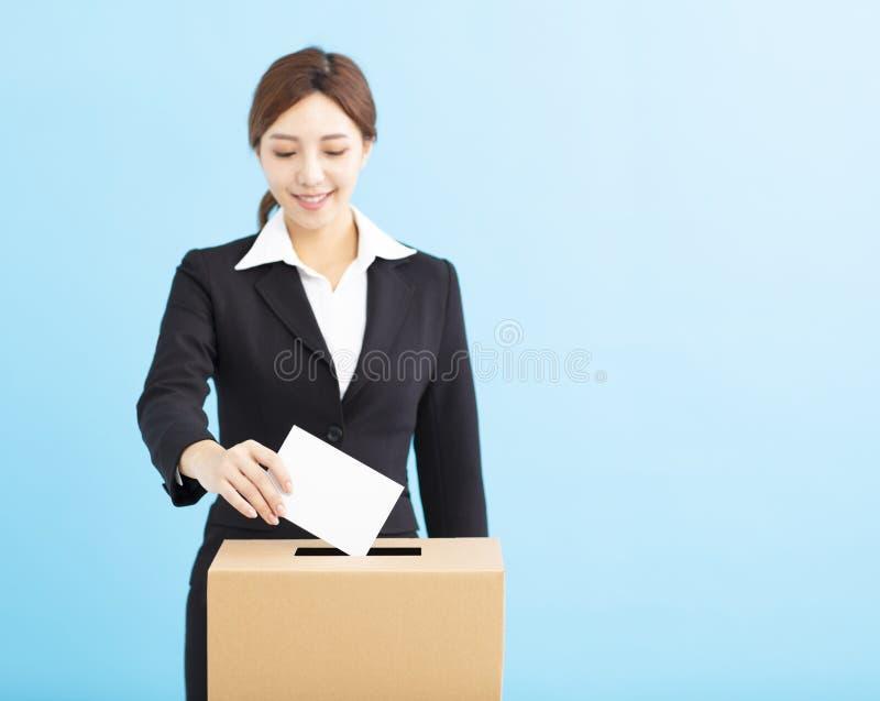 Mujer que pone la votación en la caja de votación imágenes de archivo libres de regalías