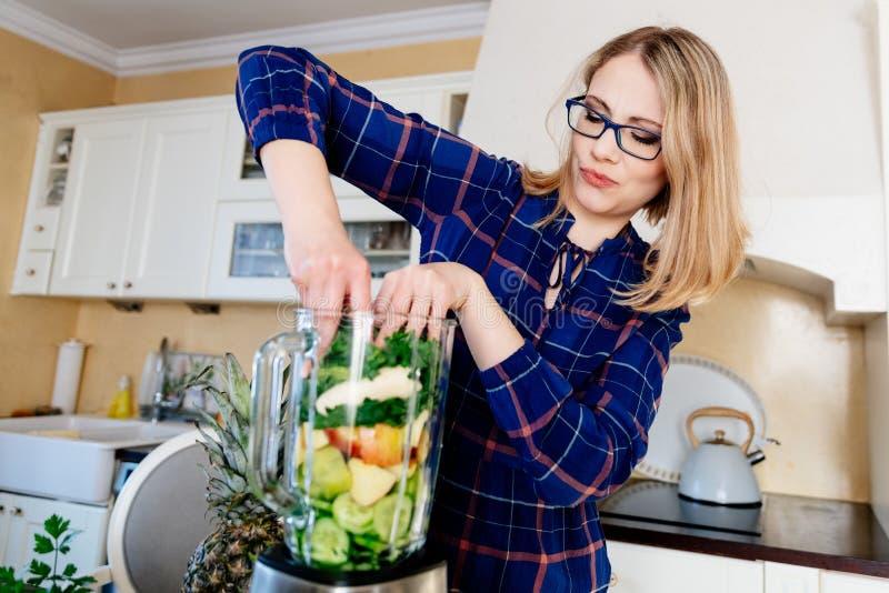 Mujer que pone las frutas y verduras en la licuadora eletrical fotografía de archivo