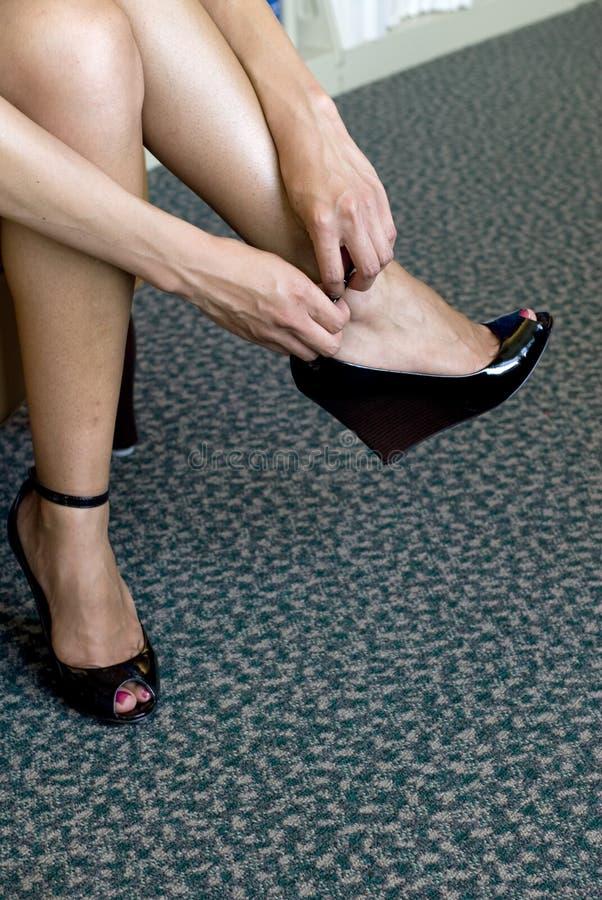 Mujer que pone los zapatos negros atractivos imagen de archivo libre de regalías