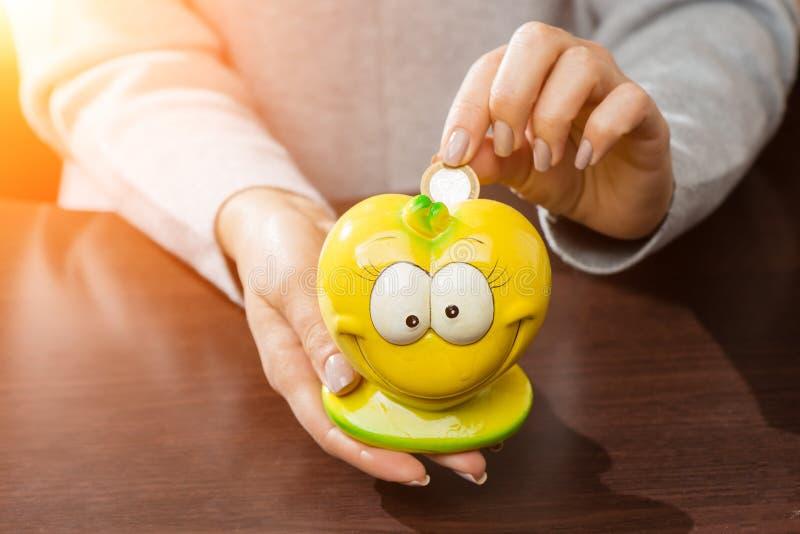 Mujer que pone monedas en un moneybox amarillo divertido en los rayos del su foto de archivo