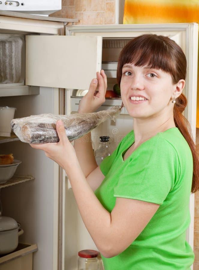 Mujer que pone pescados congelados sin procesar en refrigerato fotografía de archivo libre de regalías