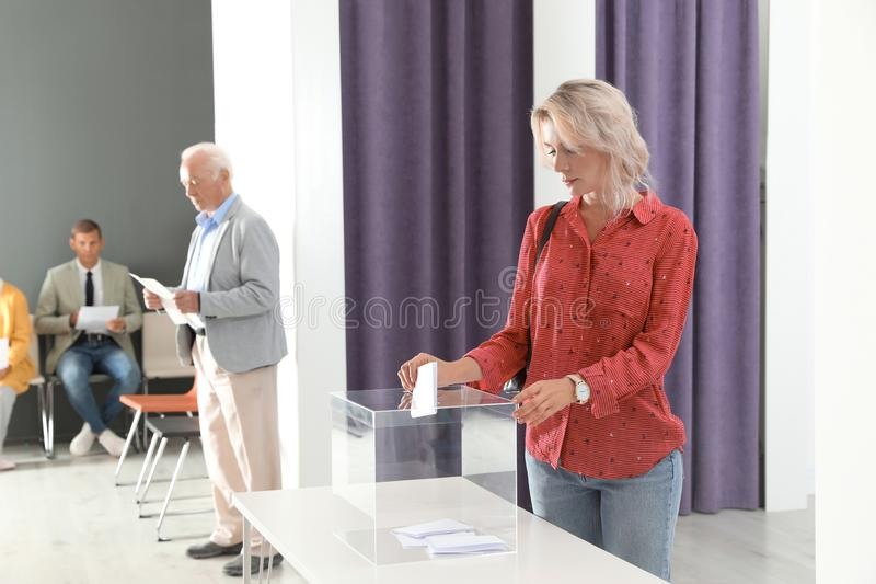 Mujer que pone su voto en la urna fotos de archivo