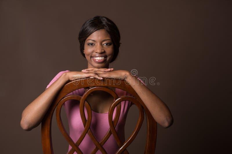 Mujer que pone sus manos en silla y la sonrisa fotos de archivo