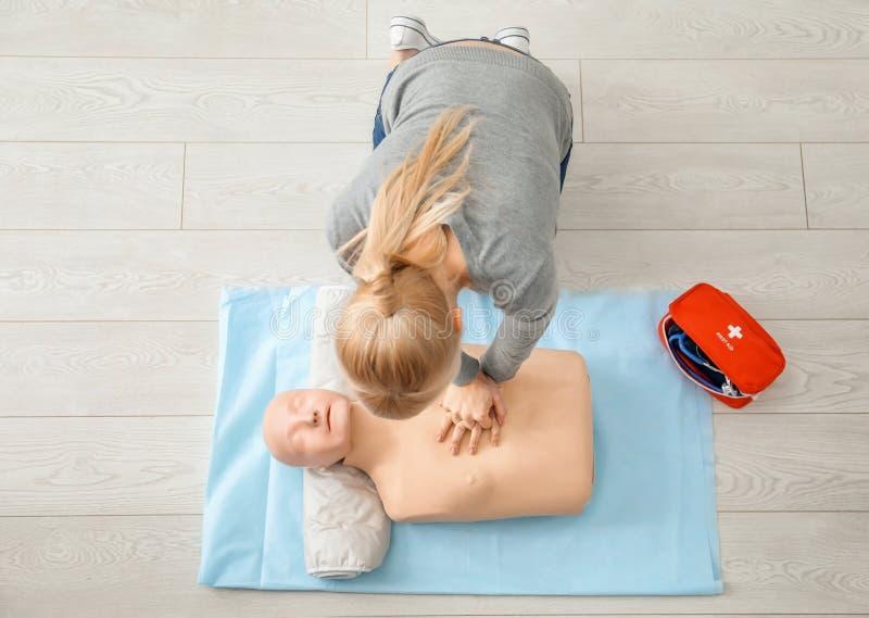 Mujer que practica el CPR en maniquí imagenes de archivo