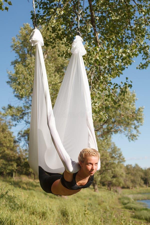 Mujer que practica yoga antigravedad en el árbol cerca del río imágenes de archivo libres de regalías