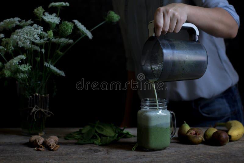 Mujer que prepara el smoothie verde y blanco con los higos, plátano, waln foto de archivo libre de regalías