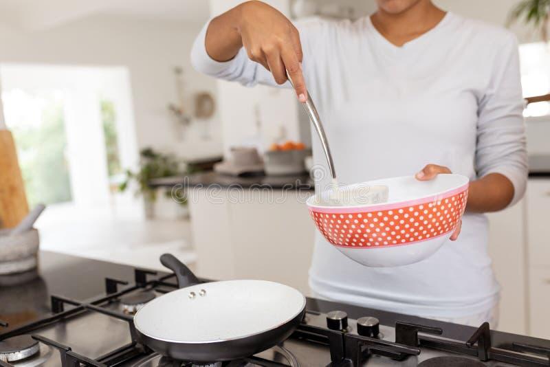 Mujer que prepara la comida en cocina en casa fotografía de archivo