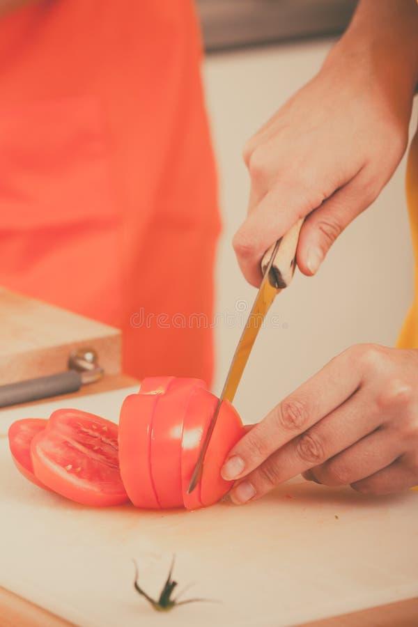 Mujer que prepara la ensalada de las verduras que corta el tomate fotografía de archivo libre de regalías