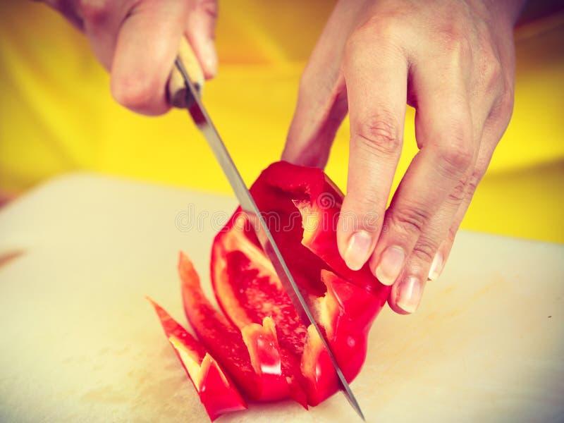 Mujer que prepara la ensalada de las verduras que corta la pimienta roja imagen de archivo libre de regalías