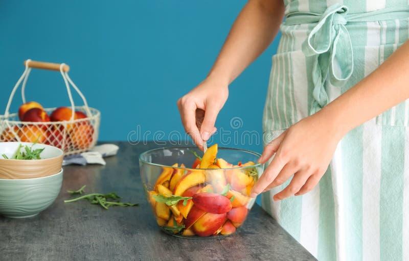 Mujer que prepara la ensalada sabrosa con los melocotones y el arugula cortados imagenes de archivo