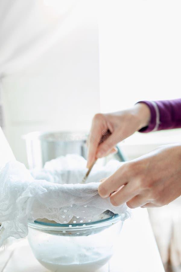 Mujer que prepara la leche de la almendra en casa fotografía de archivo