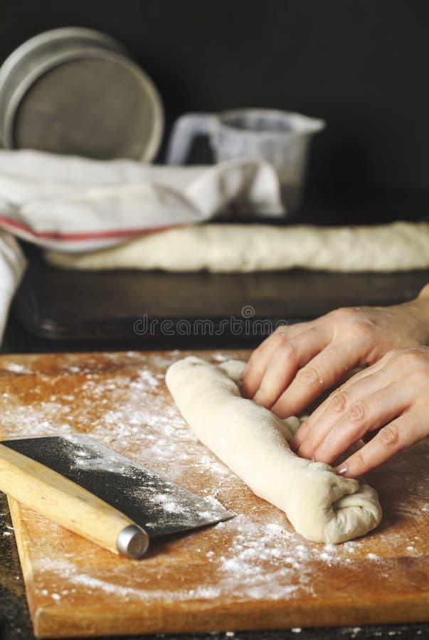 Mujer que prepara la pasta para el baguette francés imagen de archivo