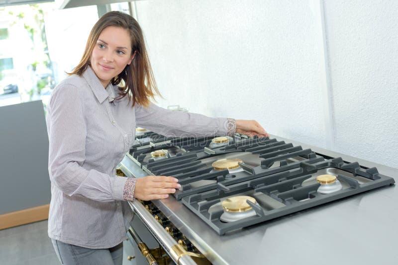 Mujer que presenta cocinando la gama imagenes de archivo