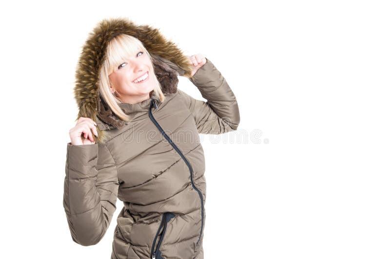 Mujer que presenta con la capilla de la chaqueta del invierno encendido y la sonrisa foto de archivo libre de regalías