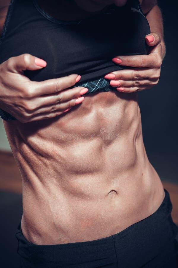 Mujer que presenta con los músculos perfectos del abdomen imagenes de archivo