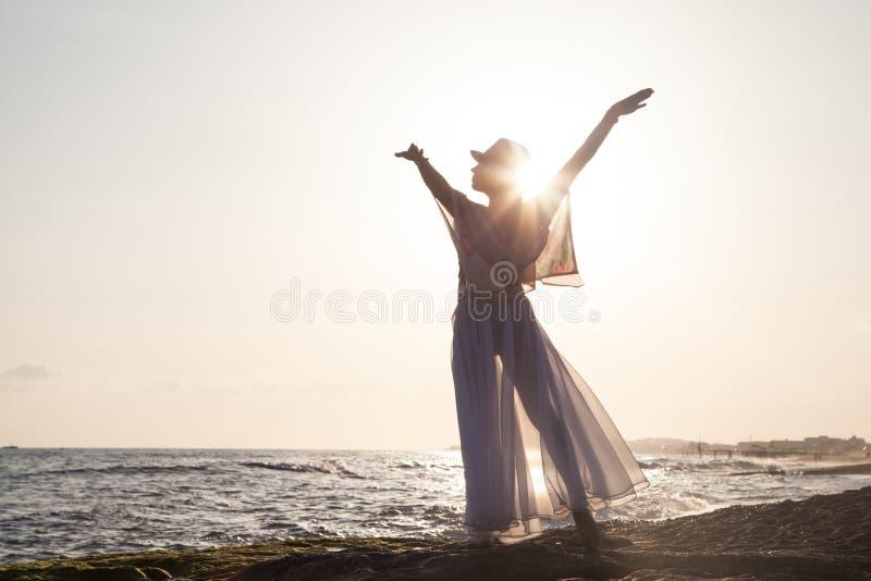 Mujer que presenta en la puesta del sol foto de archivo libre de regalías