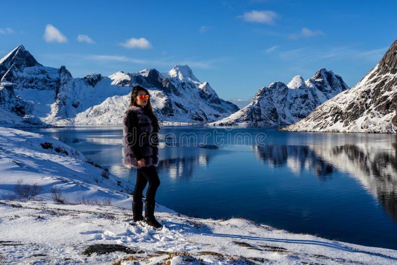 Mujer que presenta en las montañas de las islas de Lofoten Reine, Noruega imágenes de archivo libres de regalías