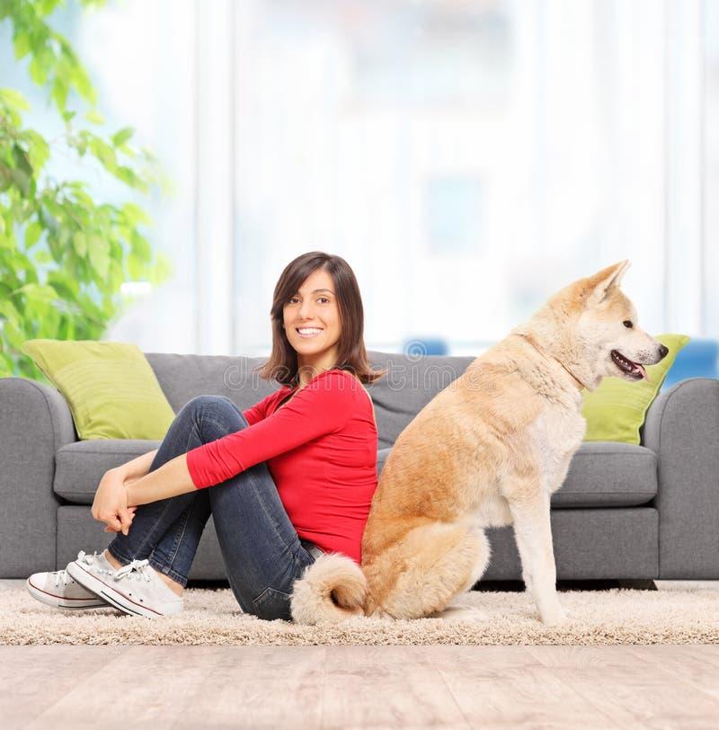 Mujer que presenta la cuba de tintura asentada para apoyar con su perro foto de archivo